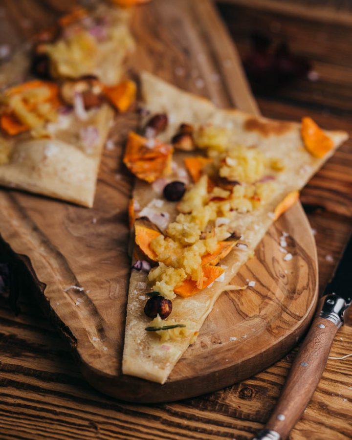 Flammkuchen auf Holzbrett mit Messer