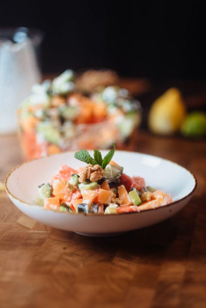 Sommer Salat auf weissem Teller mit Wassermelone, Gurke und MInze