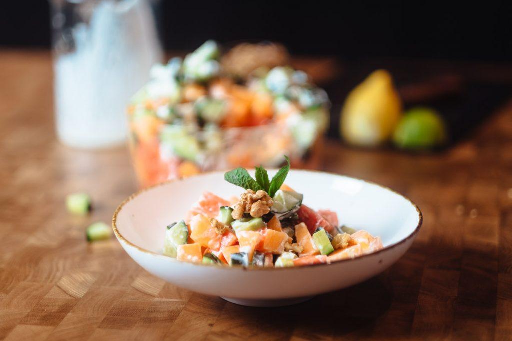 Sommer Salat mit Melone und Gurken auf weissem Teller mit Wassermelone, Gurke und MInze